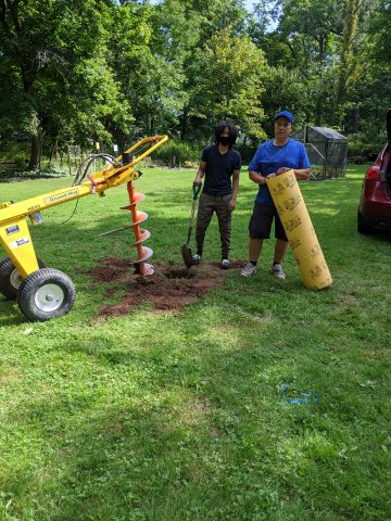 Mr. Kaiser and 8th grader, Jolia work on installing posts for the pavilion.